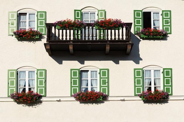 Uitzicht op het gebouw met balkon en ramen met groene luiken versierd met bloemen. Premium Foto
