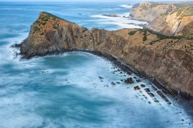 Uitzicht op het zeegezicht op de steile kliffen en wazig golven. portugal. Premium Foto