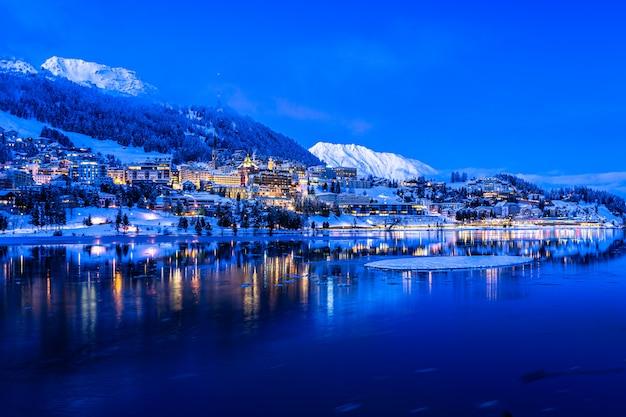Uitzicht op prachtige nachtlichten van de stad st. moritz in zwitserland 's nachts in de winter, met reflectie van het meer en de sneeuwbergen in backgrouind Premium Foto