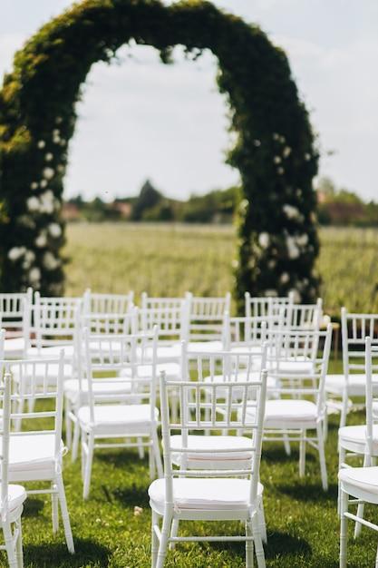 Uitzicht op witte stoelen en boog voor de huwelijksceremonie Gratis Foto