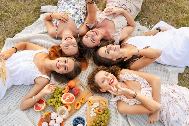 Uitzicht van boven. gezelschap van mooie vriendinnen hebben plezier en genieten van een picknick buiten. Premium Foto
