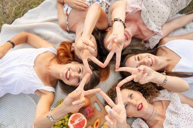 Uitzicht van boven. het gezelschap van mooie vriendinnen heeft plezier en geniet van een picknick buiten Premium Foto