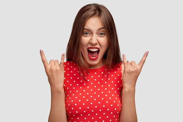 Uitzicht van coole europese vrouw maakt rock gebaar, roept met waanzin Gratis Foto