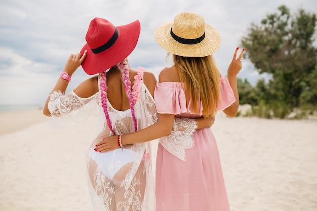 Uitzicht vanaf de achterkant op twee mooie stijlvolle vrouw op strand op vakantie, zomerstijl, modetrend, strooien hoeden dragen, modetrend, roze en kanten jurk, sexy outfit Gratis Foto