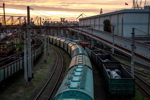 Uitzicht vanaf de spoorbrug naar goederentreinen bij zonsondergang. Gratis Foto