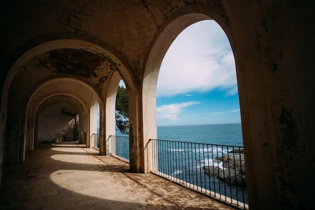 Uitzicht vanaf het oude gebouw op de oceaan of de zee met romeinse zuilen en historische ruïnes op de mediterrane kustlijn. Gratis Foto