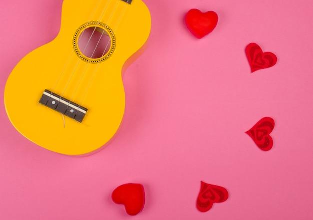 Ukelele-gitaar en rode harten die een cirkel vormen tegen een felroze achtergrond (love song-concept) Premium Foto