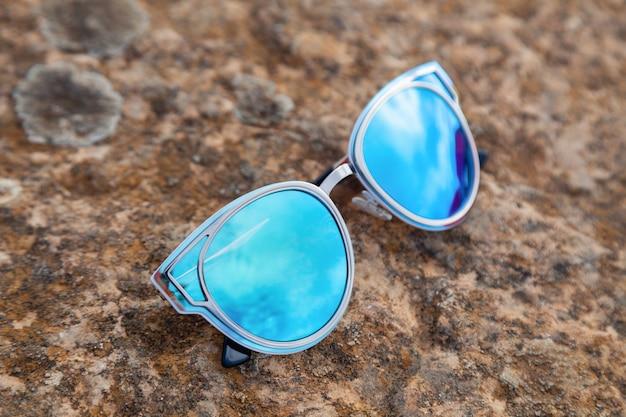 Ultraviolet van de close-up het mooie blauwgroene weerspiegelde zonnebril op grond in zonneschijn bij zonsondergang, weerspiegeling van stenen, kalksteen, wijngaard. mode-schietaccessoires voor een optiekwinkel Premium Foto