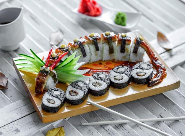 Unagi sushi rolletjes geserveerd in draakvorm en sushi yin yang Gratis Foto