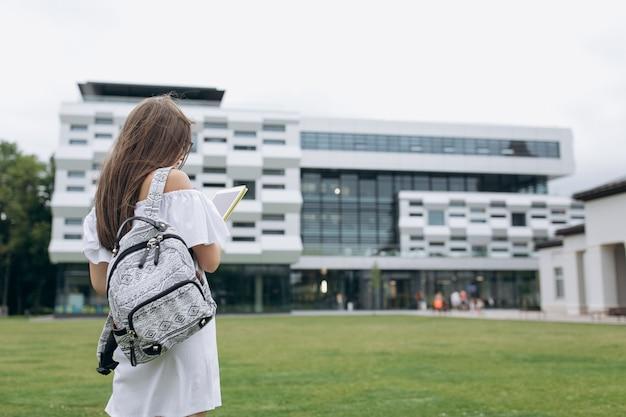 Universitaire student buitenshuis op de campus. student met rugzak. jonge gelukkige student. studenten die in openlucht op universitaire campus lopen Premium Foto
