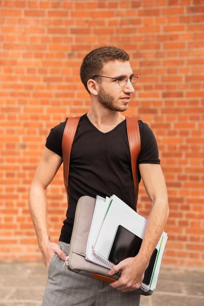 Universitaire student die zijn nota's houdt en weg kijkt Gratis Foto