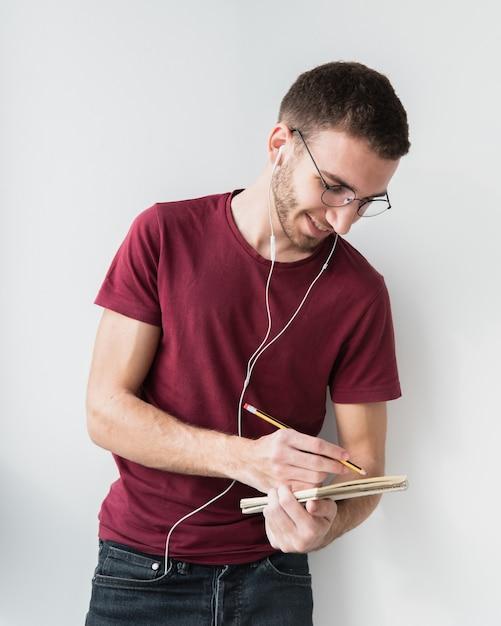 Universitaire student draagt een koptelefoon en schrijven Gratis Foto