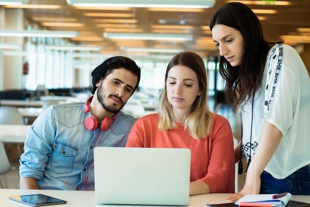 Universitaire studenten die laptop in universitaire bibliotheek met behulp van. Premium Foto
