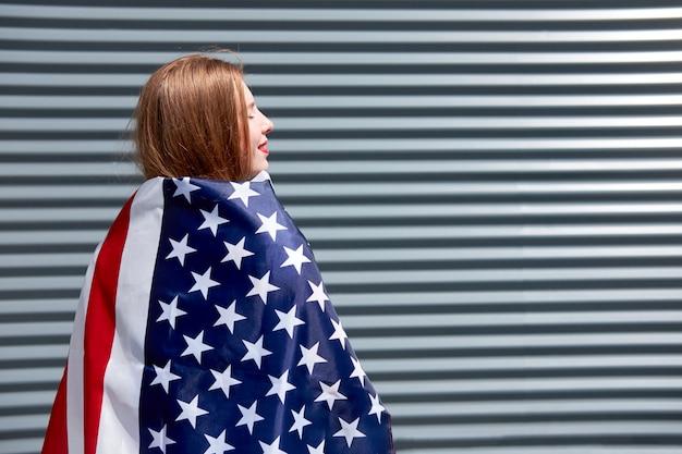 Usa sterren en strepen vlag jonge roodharige vrouw met rood geschilderde lippen staan met usa vlag grijze metalen paneel achtergrond Premium Foto