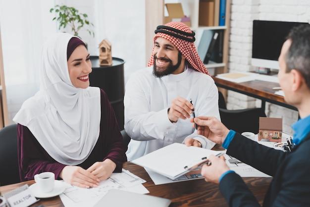 Uw handtekeningagent geeft pen aan arabische klant. Premium Foto