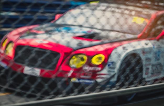 Vaag beeld van het netwerk van de omheiningsnetwerk en auto op renbaan. autosport autosport op asfaltweg. super racewagen op stratencircuit. auto-industrie concept. Premium Foto