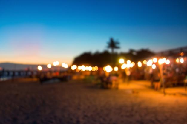 Vaag zeevruchtenrestaurant bij het strand met mooie zonsonderganghemel als achtergrond Premium Foto