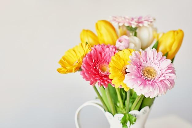 Vaas met boeket van mooie tulpen en gerbera's Premium Foto