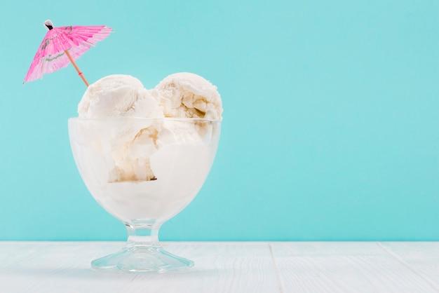 Vaas met vanille-ijs met roze paraplu erop Gratis Foto