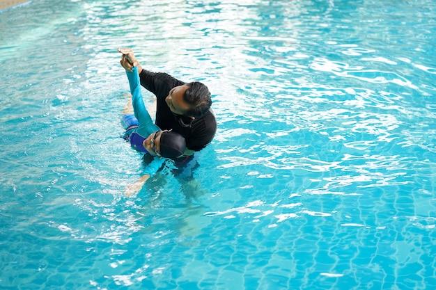 Vader die dochter onderwijzen om in een zwembad te zwemmen Premium Foto