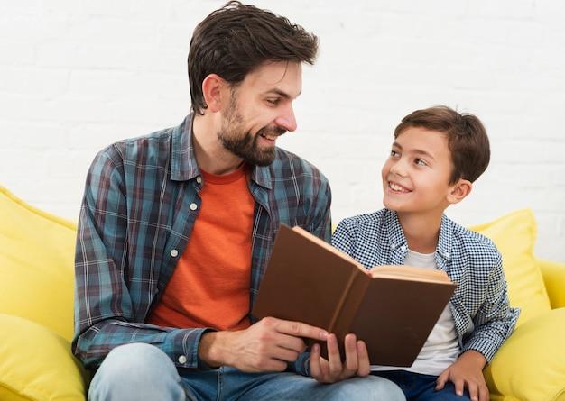 Vader die een boek houdt en zijn zoon bekijkt Gratis Foto