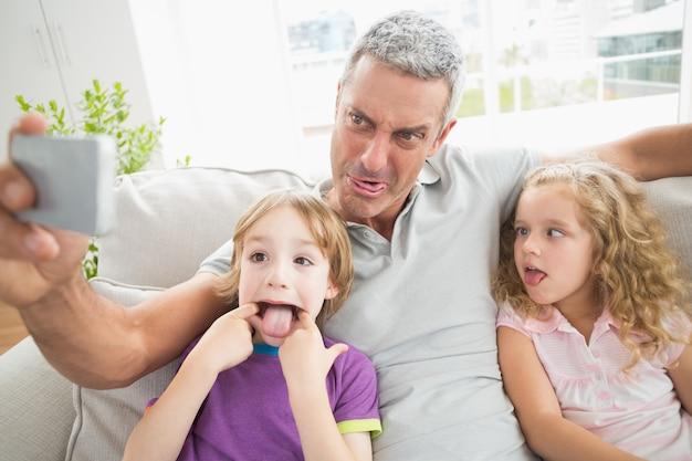 Vader die gezicht maakt terwijl het nemen selfie met kinderen Premium Foto