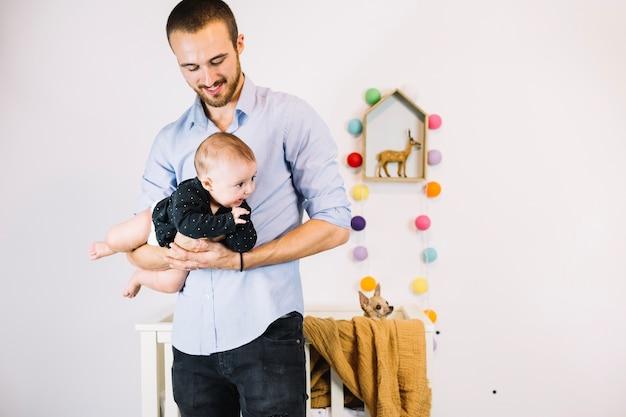Vader die glimlachende baby houdt Gratis Foto