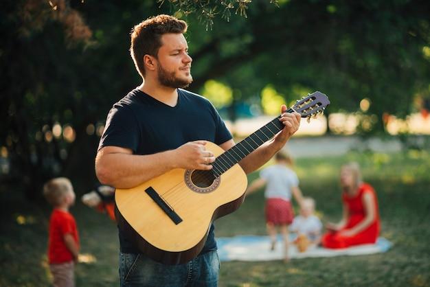 Vader die op klassieke gitaar speelt Gratis Foto