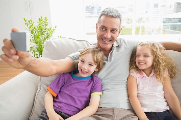 Vader die selfie met kinderen op bank neemt Premium Foto