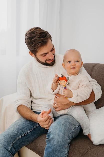 Vader die thuis zijn baby vasthoudt Gratis Foto