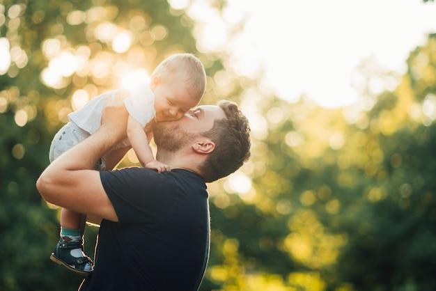 Vader die zijn baby in het park kust Gratis Foto