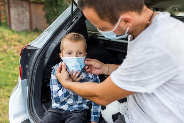 Vader die zijn zoons medisch masker schikt Gratis Foto