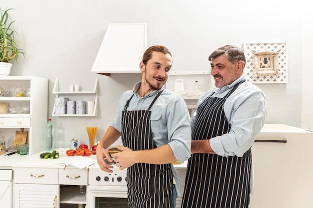 Vader die zoon met keukenschort helpt Gratis Foto