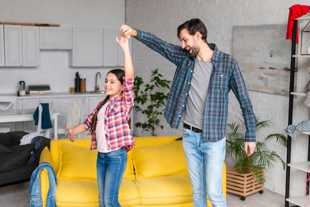Vader en dochter dansen in de woonkamer Gratis Foto