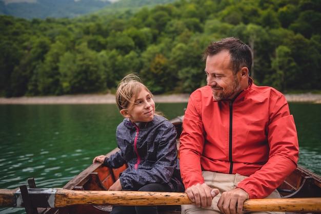 Vader en dochter die een boot op het meer roeien Premium Foto