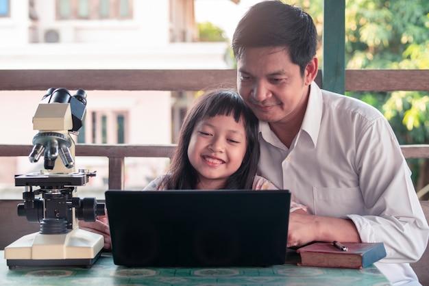 Vader en dochter die en van huis met laptop en microscoop glimlachen leren Premium Foto