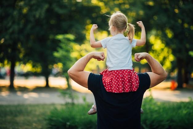 Vader en dochter die hun spieren tonen Premium Foto