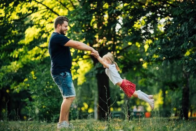 Vader en dochter die in cirkel spinnen Gratis Foto