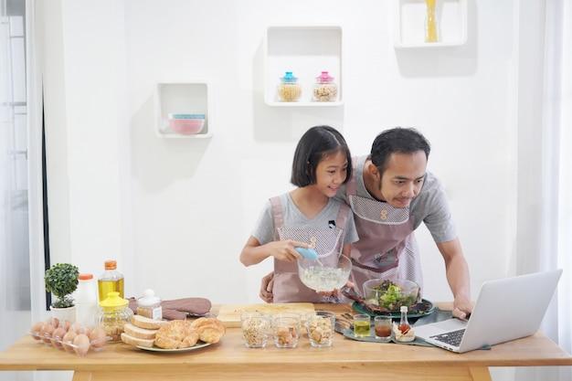 Vader en dochter die online het koken gebruiken die laptop computer in de keuken thuis met behulp van Premium Foto