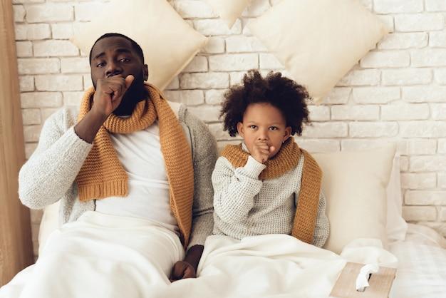 Vader en dochter die thuis op bed hoesten. Premium Foto