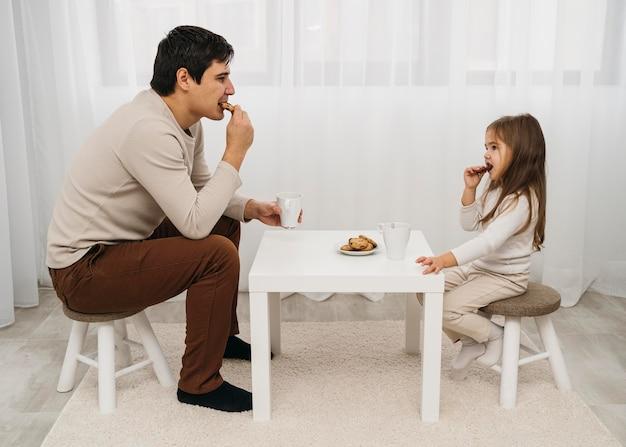 Vader en dochter die thuis samen eten Gratis Foto