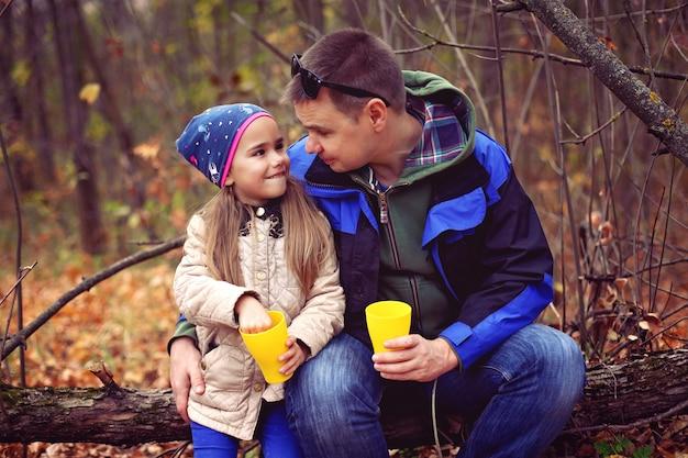 Vader en dochter het drinken van thee in het de herfstbos Premium Foto