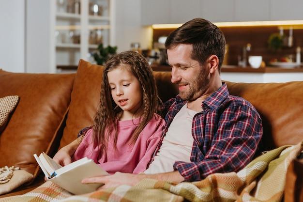 Vader en dochter leesboek thuis Gratis Foto