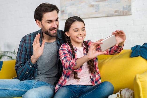 Vader en dochter praten met iemand op video-oproep Gratis Foto