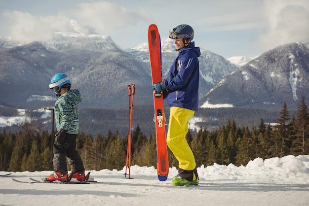 Vader en dochter skiën op besneeuwde alpen Gratis Foto