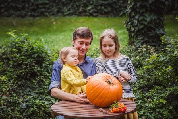 Vader en dochter snijdende pompoen voor halloween Premium Foto