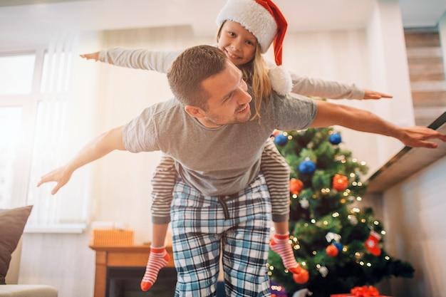 Vader en dochter spelen in de kamer. hij berijdt haar op zijn rug. ze houden hun handen opzij van het lichaam. jonge man kijkt naar meisje. ze lachen. Premium Foto
