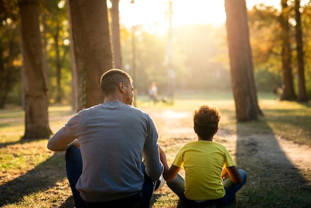 Vader en dochter zittend op het gras in park genieten van zonsondergang samen Gratis Foto