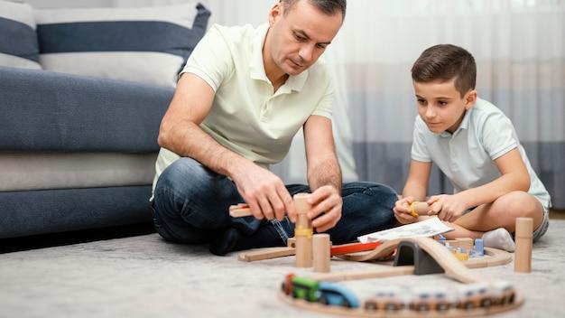Vader en kind spelen binnenshuis samen Gratis Foto