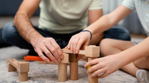 Vader en kind spelen met speelgoed vooraanzicht Gratis Foto